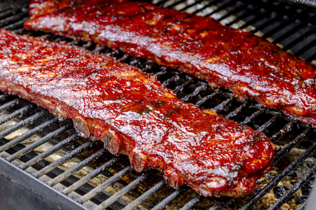Two racks of pork ribs with barbeque sauce sitting on grill Imagens
