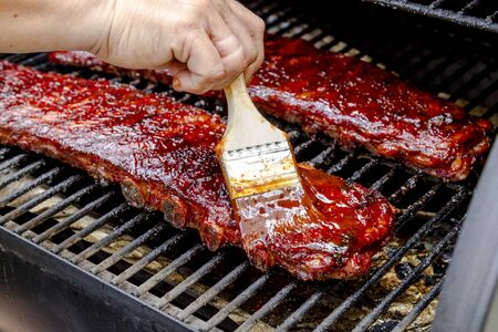 Close up of two racks of pork bbq ribs sitting on grill with hand applying barbeque sauce with brush Stock Photo