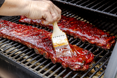 Two racks of pork bbq ribs sitting on grill with hand applying barbeque sauce with brush