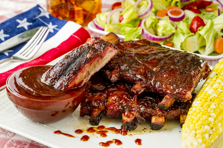 Close up of single pork rib sitting in cup of barbeque sauce on white plate with stack of bbq pork ribs, corn on the cob with side salad and glass of iced tea Imagens