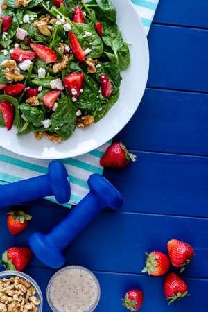 Fresh organic strawberry spinach salad with walnuts, feta cheese and poppy seed dressing on dark blue background with blue weights and salad ingredients and space for text Stock Photo