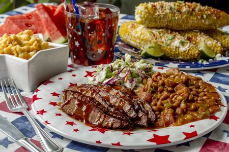 Picnic table filled with meal of barbecue beef brisket with beans, coleslaw, corn on the cob and watermelon