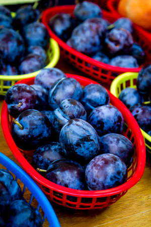Colorful baskets filled with blue plums for sale at local farmers market Stock Photo