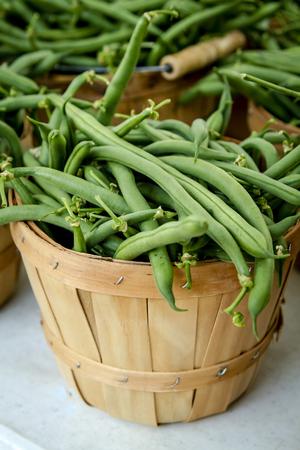 long bean: Fresh organic green long beans in brown bushel basket display Stock Photo