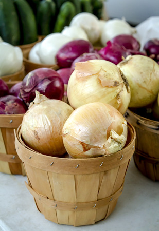 Yellow, red and white onions in bushel basket display at outdoor market