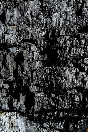 Black coal in rock canyon wall textured background