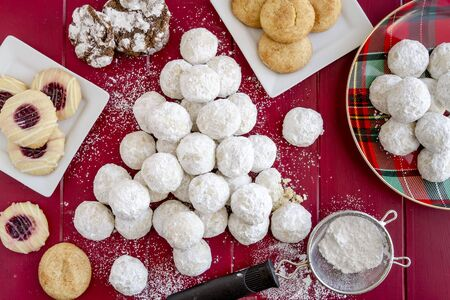 Home baked tea cookies rolled in powdered sugar, arranged in shape of a Christmas tree surrounded by a variety of Christmas cookies Stock Photo