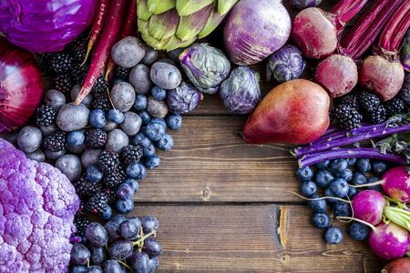 Close up of background of purple fruits and vegetables on wooden table with opening for text