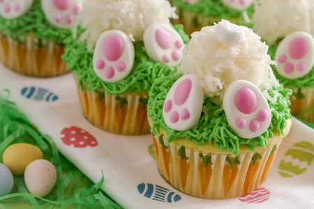 Close up of row of Easter bunny butt cupcakes made with lemon cake and filled with lemon curd sitting on Easter egg napkin in green grass and candy eggs