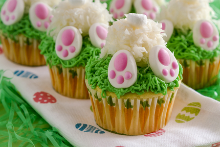 Row of Easter bunny butt cupcakes sitting on Easter egg napkin surrounded by green grass Stock Photo