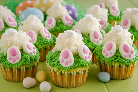 Easter bunny butt cupcakes made with lemon cake and filled with lemon curd with colorful polka dot Easter eggs in background