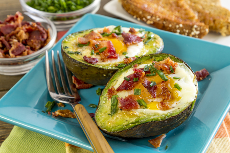 Healthy low carb paleo breakfast of baked avocado and eggs boats with bacon crumbles and chives and whole wheat toast in background