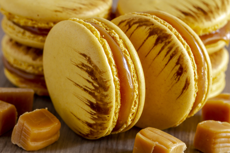 Close up of salted caramel flavored french macarons surrounded by bits of caramel