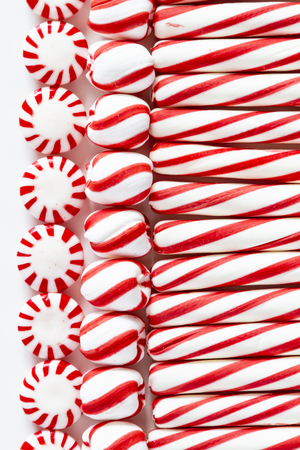 Candy background of red and white striped peppermint sticks, starlight mints and swirled candy balls Stock Photo