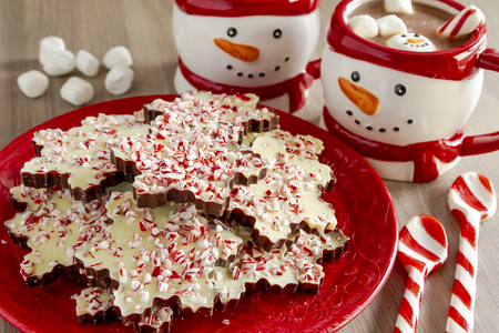 Snowflake shaped chocolate peppermint bark on red holiday plate with snowman mugs filled with hot cocoa, marshmallows and peppermint spoons