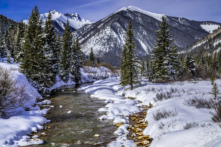Winter landscape of Colorado San Juan mountains and alpine forest covered with freshly fallen snow with river running up the valley off of Red Mountain Pass near the town of Silverton