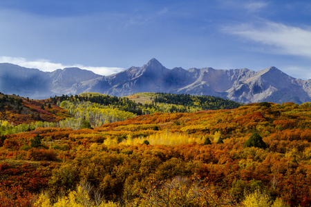 Dallas Divide in full fall color in early morning light with low clouds and blue skies in San Juan Mountains