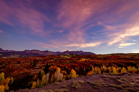 Colorful pink sunset along Dallas Divide in Colorado with changing fall colors