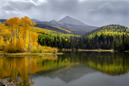 Fall afternoon sunshower reflecting in mountain lake with changing aspen trees and pine forest on the shore and mountain peaks in clouds