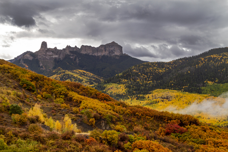 Colorful mountainside of yellow aspen trees and orange scrub oak along Owl Creek Pass with Courthouse Mountain and Chimney Rock on stormy autumn afternoon