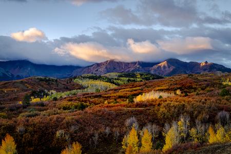 Sonnenaufgang auf den Gipfeln entlang der Dallas Divide in der Nähe von Ridgway Colorado während der Herbstfarbe mit gelben Espenbäumen und orangefarbener Eiche im Tal