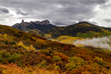 Colorful mountainside of yellow aspen trees and orange scrub oak along Owl Creek Pass with Courthouse Mountain and Chimney Rock in distance and storm clouds in the sky Stockfoto