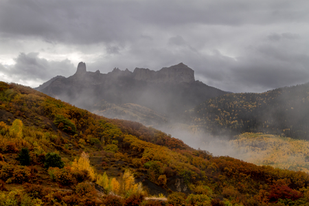 Low stormy clouds surrounding Courthouse Mountain and Chimney Rock with changing yellow aspen trees and orange scrub oak along Owl Creek Pass Stockfoto