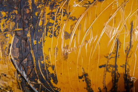 Texture of rusted piece of metal with oranges and browns lines and swirls