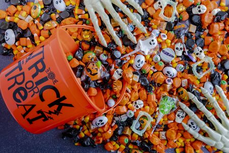 Orange trick or treat pail spilling Halloween candy on black stone surface
