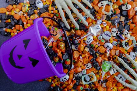 Purple pumpkin bucket spilling Halloween candy on black stone surface with skeleton hands grabbing candy Stock Photo