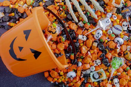 Orange pumpkin bucket spilling Halloween candy on black stone surface with skeleton hands grabbing candy