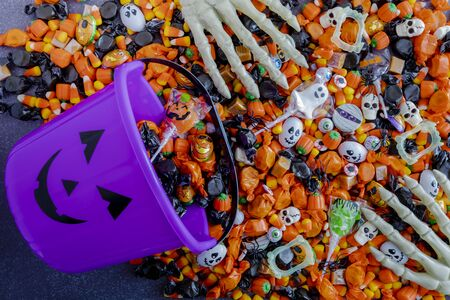 Purple pumpkin pail spilling Halloween candy on black stone surface with skeleton hands grabbing candy