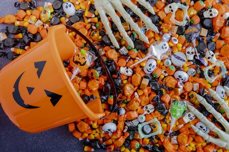 Orange pumpkin pail spilling Halloween candy on black stone surface with skeleton hands grabbing candy