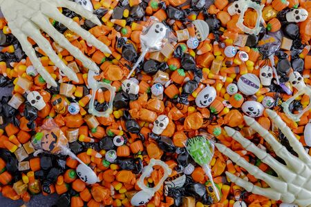 Assortment of Halloween candy on black stone surface with skeleton hands grabbing candy Stock Photo