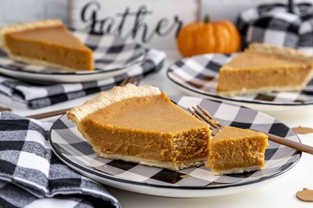 Close up of homemade pumpkin pie slice with bite taken out of slice sitting on black and white checkered plate with fork and matching napkin on festive holiday table