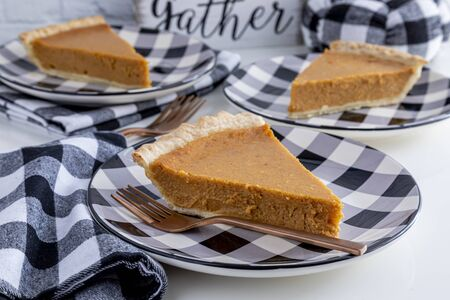 Homemade pumpkin pie slices sitting on black and white checkered plates with forks and napkins