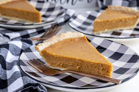 Close up of homemade pumpkin pie slices sitting on black and white checkered plates with forks and napkins