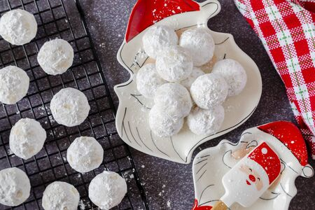 Close up of holiday snowball cookies on Santa plate with Santa spoon holder and red and white plaid napkin and additional cookies on wire baking rack