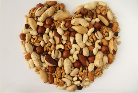 durability: Assorted nuts in the form of hearts on a white background