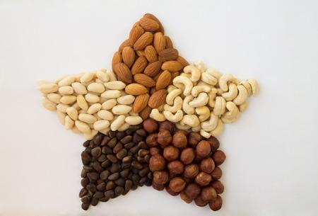 pinoli: Noci assortiti in una stella di arachidi mandorle nocciole pino anacardi noci su uno sfondo bianco