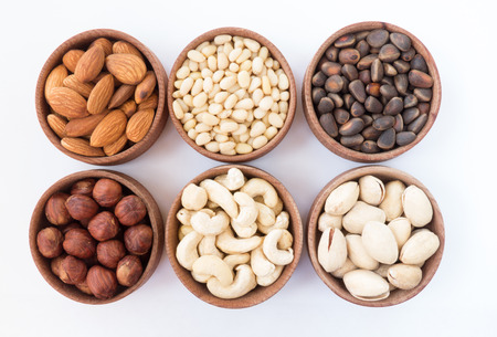 Six types of nuts in a round wooden form almonds hazelnuts pine nuts cashews pistachio on a white background photo