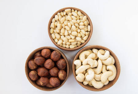 pine three: Three types of nuts in a round wooden form hazelnuts pine nuts cashews on a white background