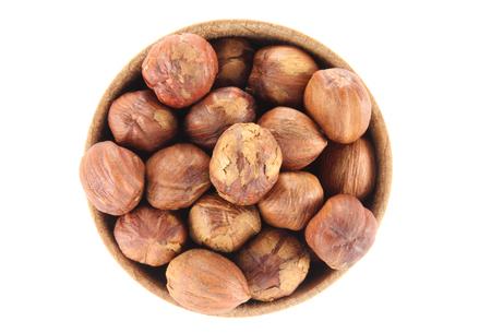 Hazelnut in a round wooden form on a white background photo