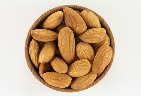 Almonds in a round wooden form on a white background photo