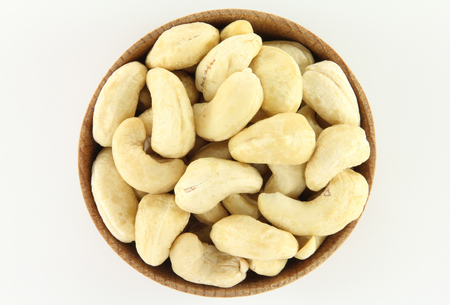 phosphorus: Cashew in a round wooden form on a white background Stock Photo