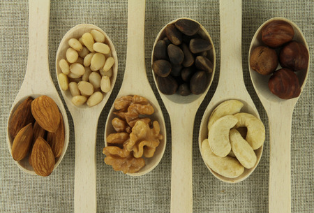 kitchen utensils: Vista abstracta de una cucharadita de frutos secos sobre un fondo de tejidos naturales Foto de archivo