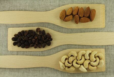 Abstract view of a wooden shovel with mixed nuts on a background of natural fabrics photo