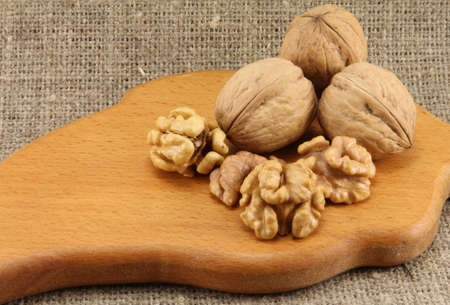 durability: Walnuts on a wooden board cutting board on a background of natural burlap