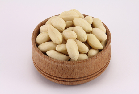 Peanuts in a round wooden form on a white background photo