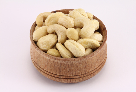 durability: Cashews in a round wooden form on a white background